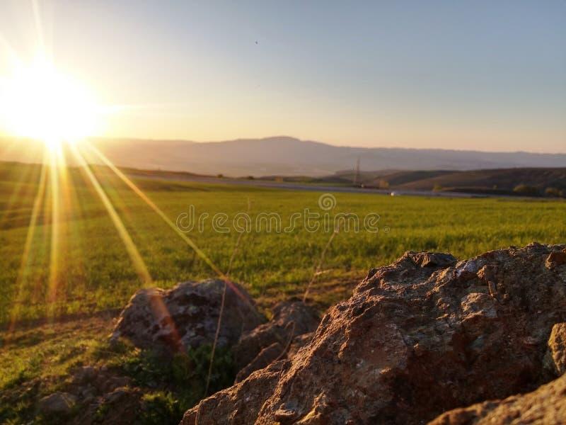 Roche et coucher du soleil image stock