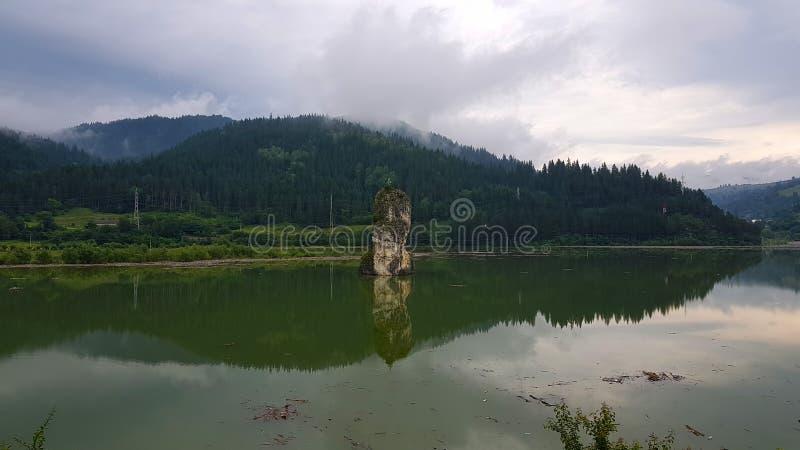 Roche et lac, entourés par la forêt images stock