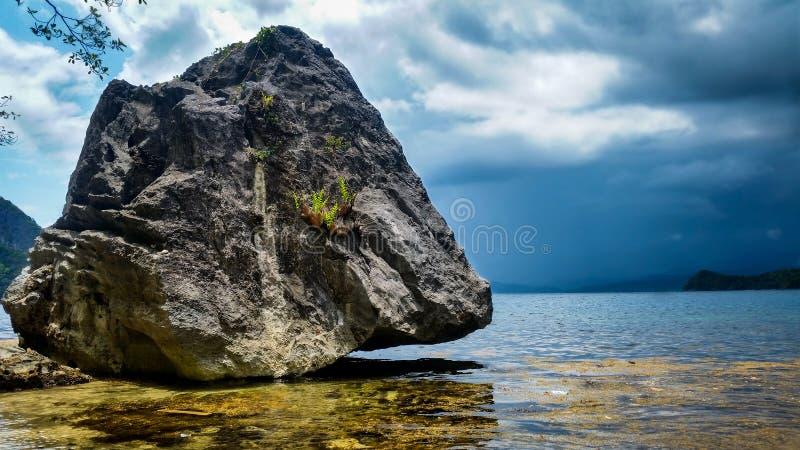 Roche géante se tenant au-dessus de l'océan un jour orageux photo libre de droits