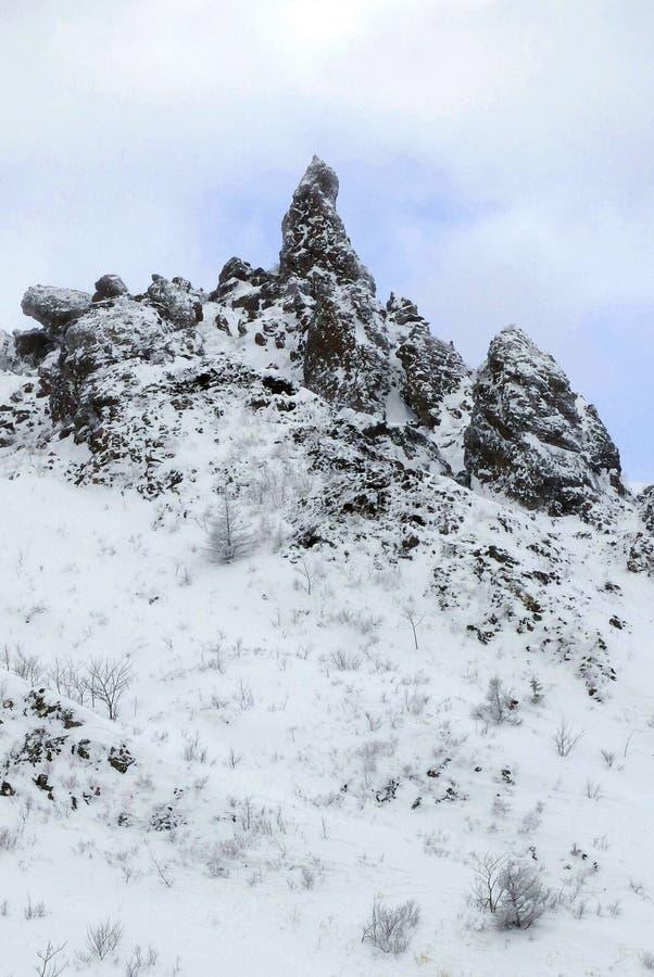 Roche noire couverte par le fond de neige en ciel bleu image libre de droits