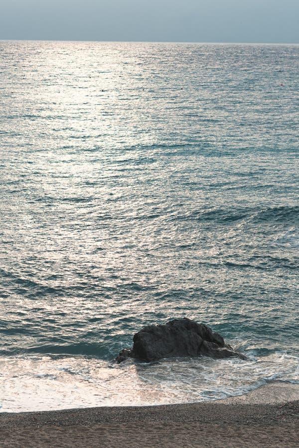 Roche simple en mer pendant l'aube de matin photo libre de droits