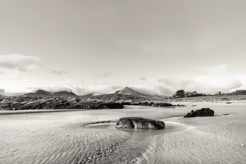 Roche sur un sable dans l'eau sur la mar?e basse en plage de Brandon photographie stock libre de droits
