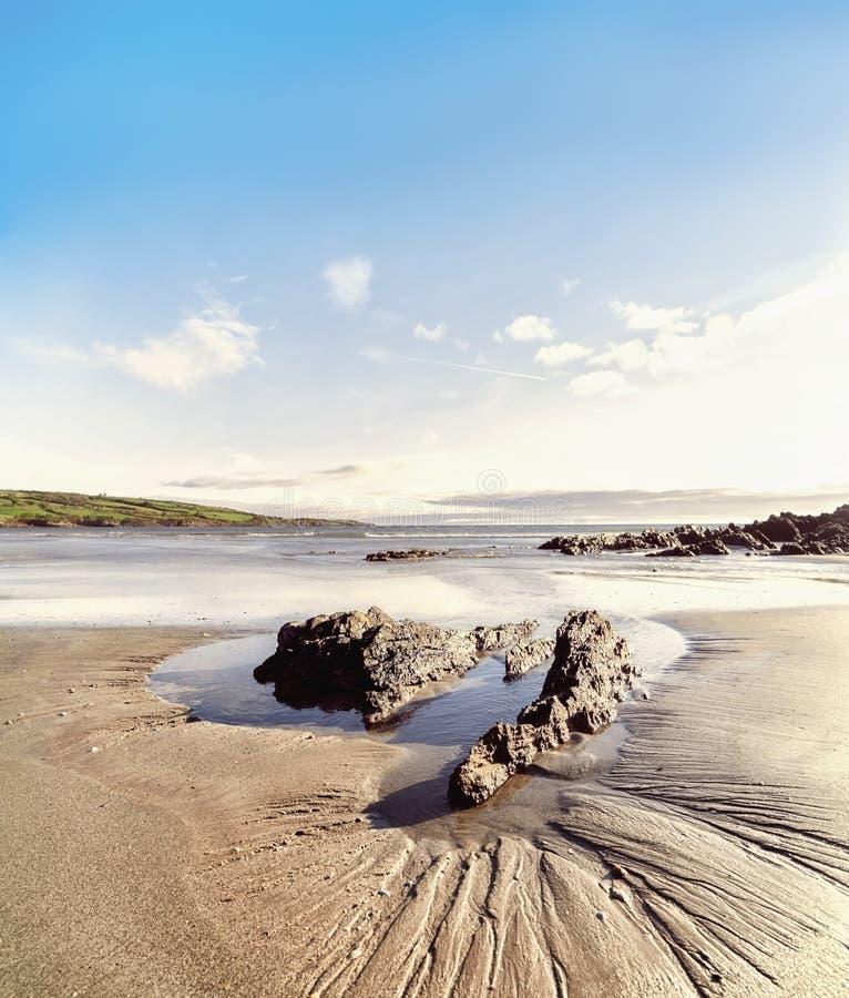 Roche sur un sable dans l'eau sur la mar?e basse en plage de Brandon photo stock