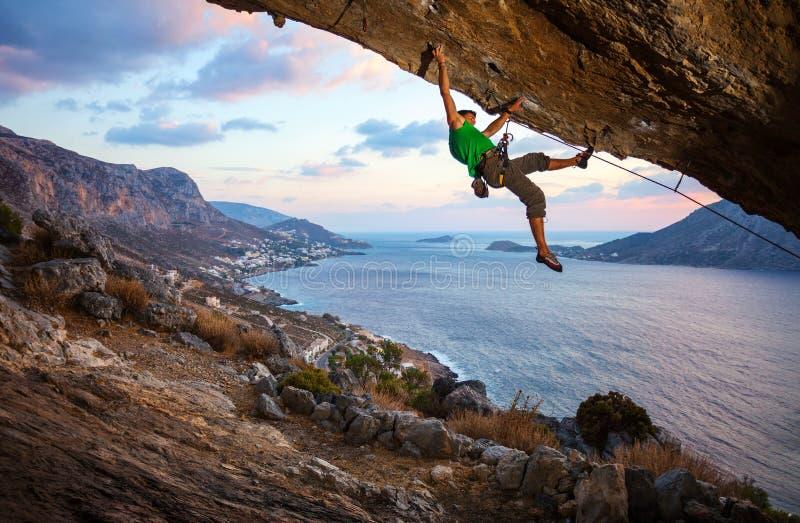 Roche surplombante s'élevante de grimpeur masculin image stock