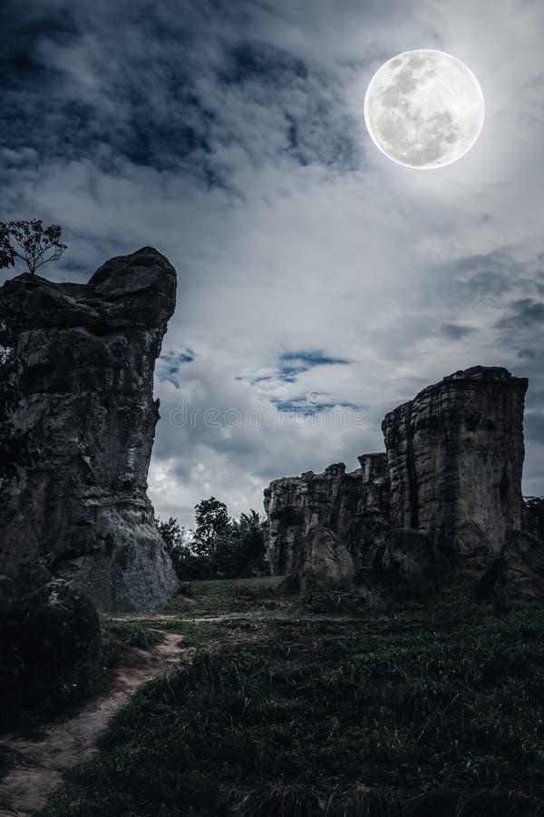 Rochers contre le ciel avec les nuages et la belle pleine lune à proche image libre de droits