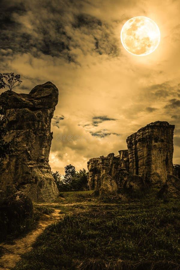 Rochers contre le ciel avec les nuages et la belle pleine lune à proche photographie stock libre de droits