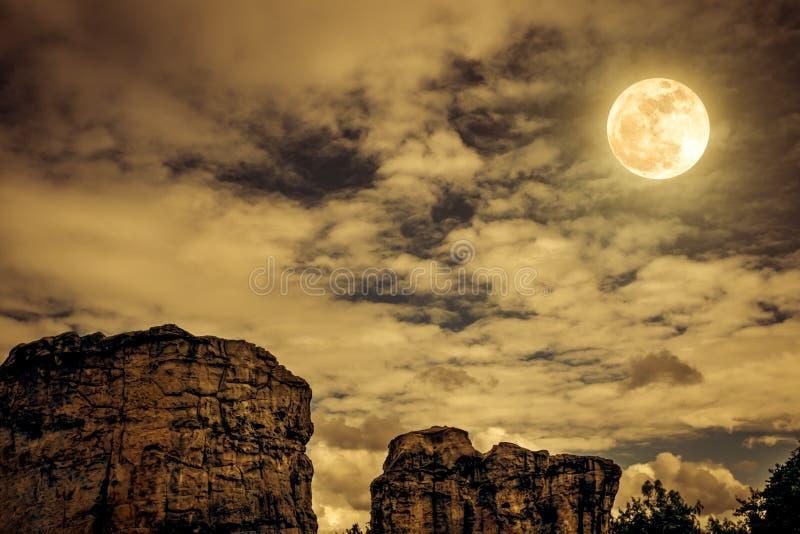 Rochers contre le ciel avec les nuages et la belle pleine lune à proche photo stock