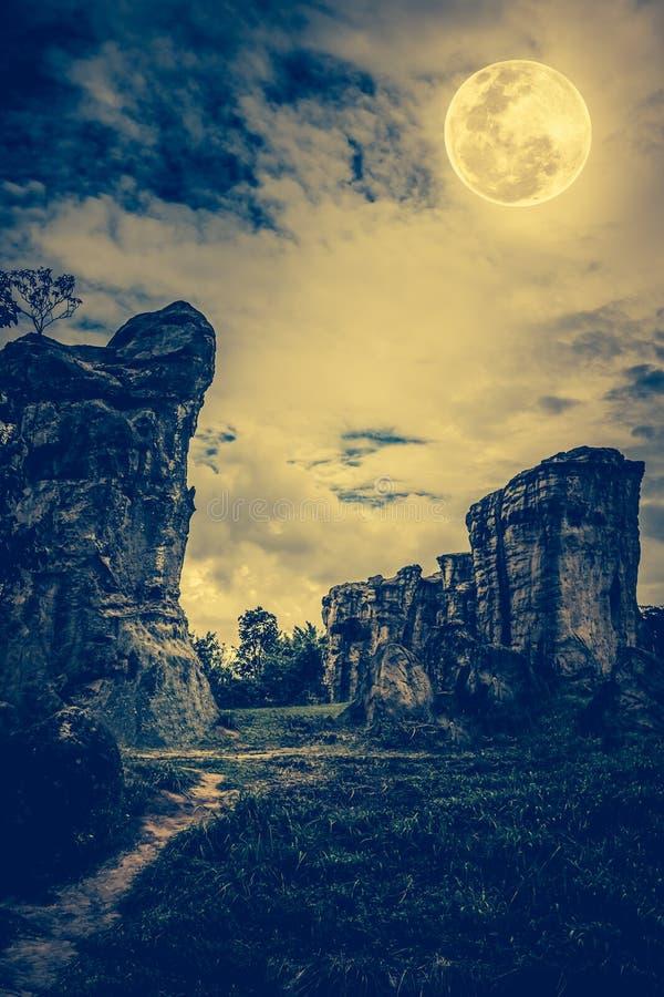 Rochers contre le ciel avec les nuages et la belle pleine lune à proche photo libre de droits