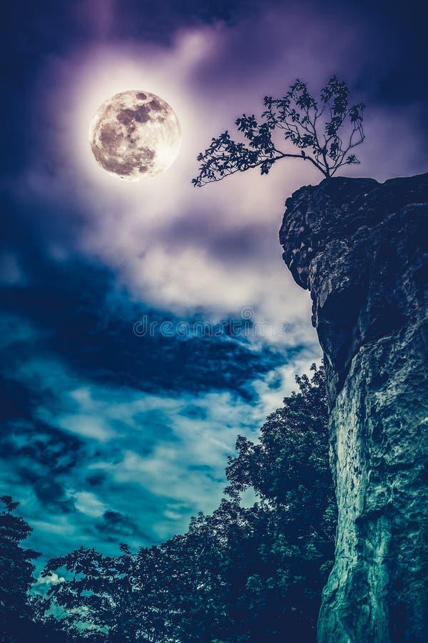 Rochers contre le ciel avec pleine la lune nuageuse et belle Croix photo stock