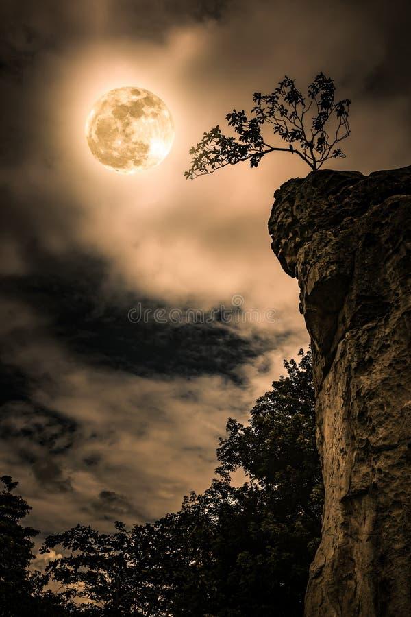 Rochers contre le ciel avec pleine la lune nuageuse et belle Vintag photographie stock