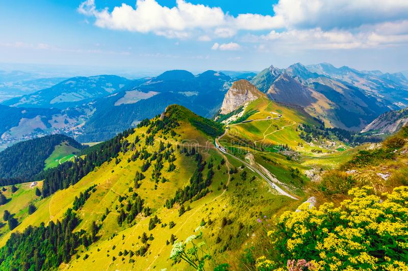 Rochers de Naye peak, Alps Mountains, Switzerland. Scenic summer panorama from Rochers de Naye mountain peak with green grassy hills and flower meadows in Alps royalty free stock photo