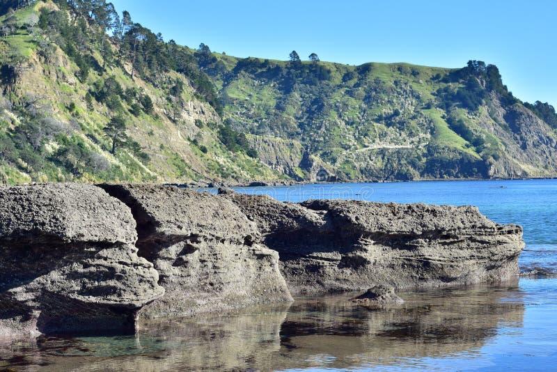 Roches côtières émergeant de la mer photos stock