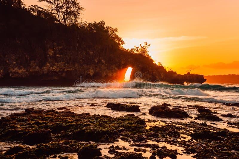 Roches dans l'océan avec des vagues et coucher du soleil lumineux à la plage images stock