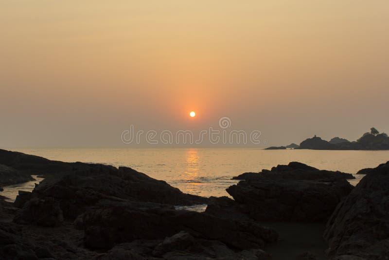 Roches dans les ombres sur le fond d'un chemin du soleil dans la mer sous un ciel rose pourpre de coucher du soleil images libres de droits