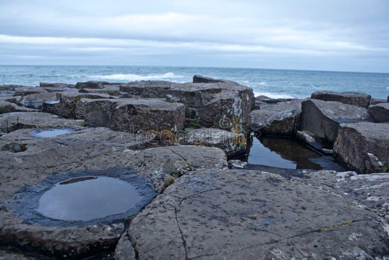 Roches de chaussée de Giants avec des magmas sur des certains roches et océan derrière images libres de droits