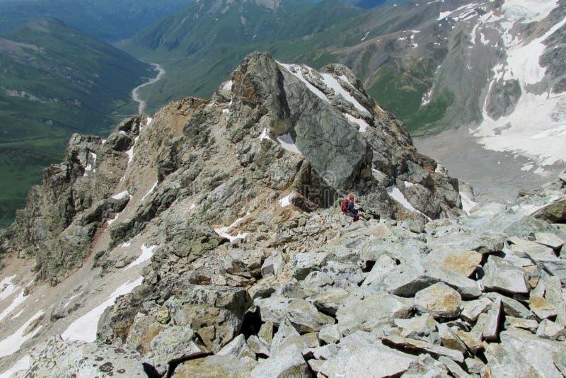 Roches de montagne et deux petits chiffres d'homme là-dessus photos stock