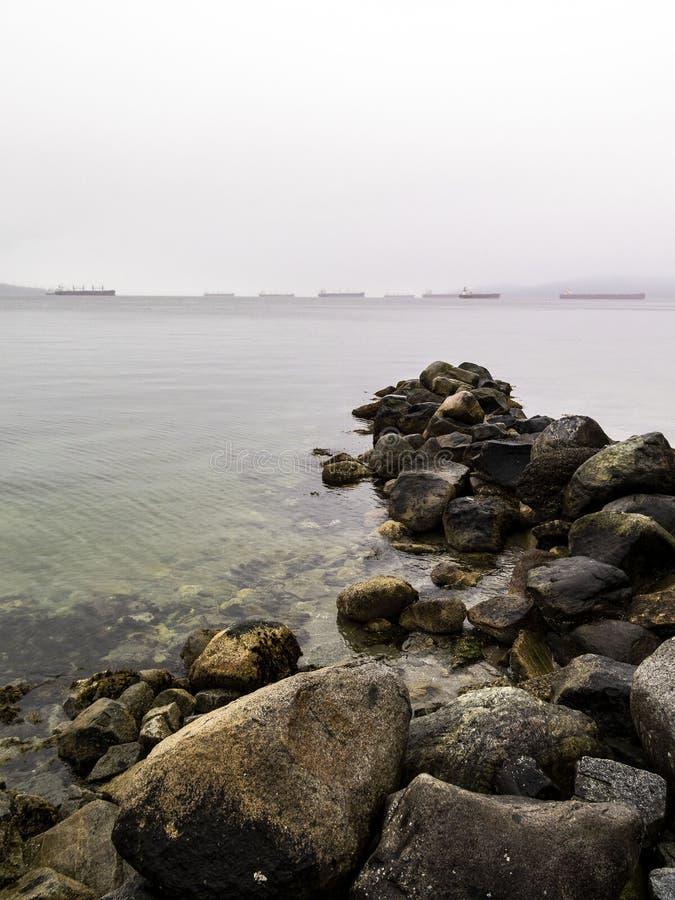 Roches en mer à la digue de parc de Stanley à Vancouver avec des cargos au fond dans le brouillard images libres de droits