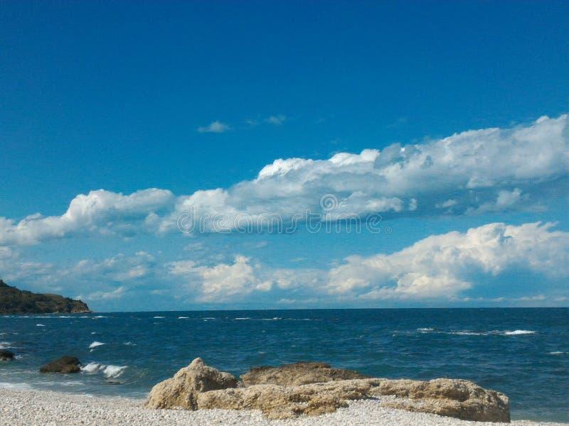 Roches et plage sous le ciel bleu images stock