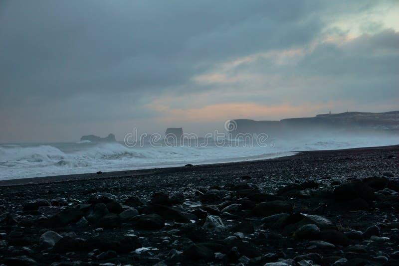 Roches noires avec les vagues formidables à l'arrière-plan à la plage de Reynisfjara en Islande image stock
