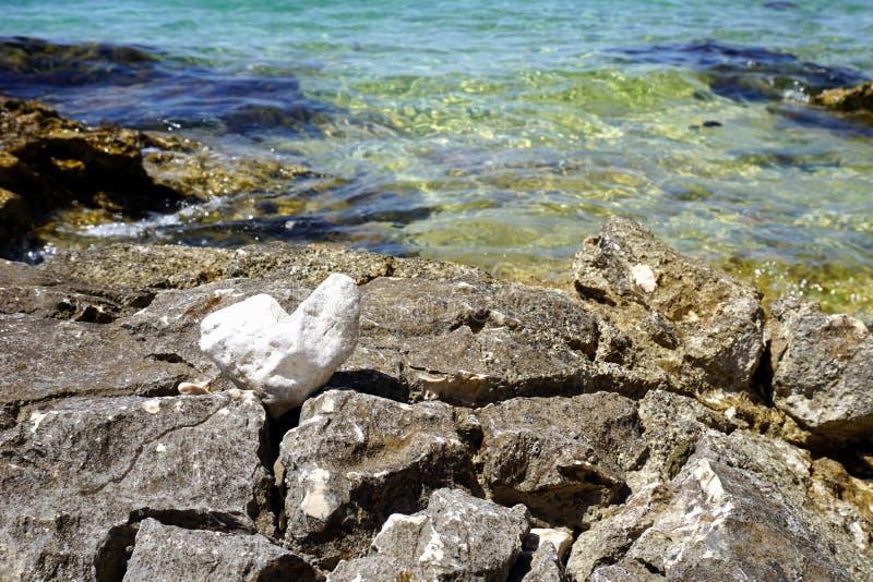 Roches par la côte et un caillou en forme de coeur devant la surface bleue de mer photos stock