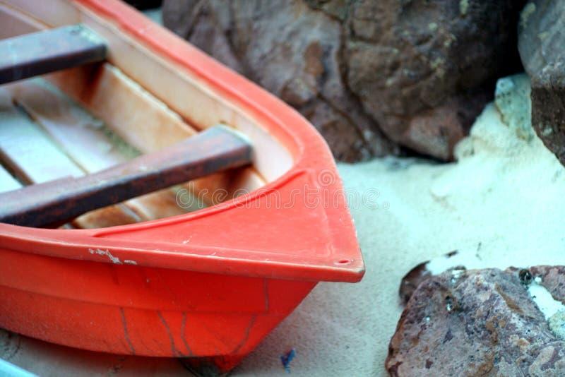 Roches rouges de bateau et de plage photographie stock libre de droits