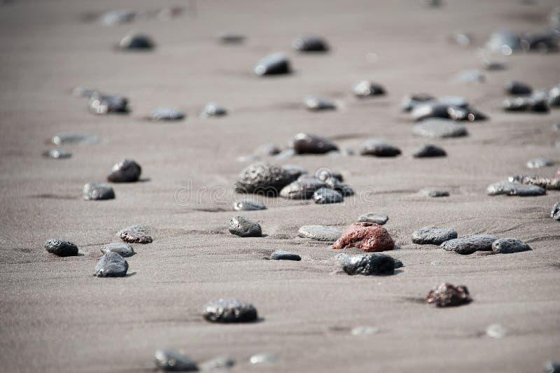 Roches sur la plage noire de sable photographie stock