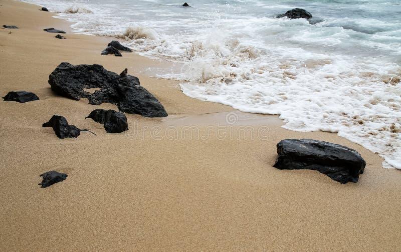 Roches volcaniques noires sur la plage de l'océan pacifique photographie stock libre de droits