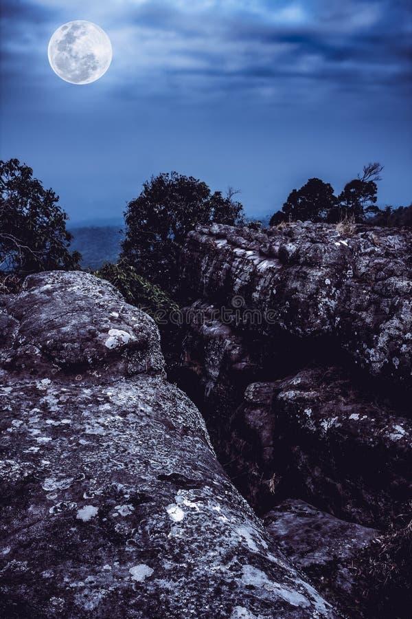 Rocheux contre le ciel bleu et la belle pleine lune la nuit extérieur photos libres de droits