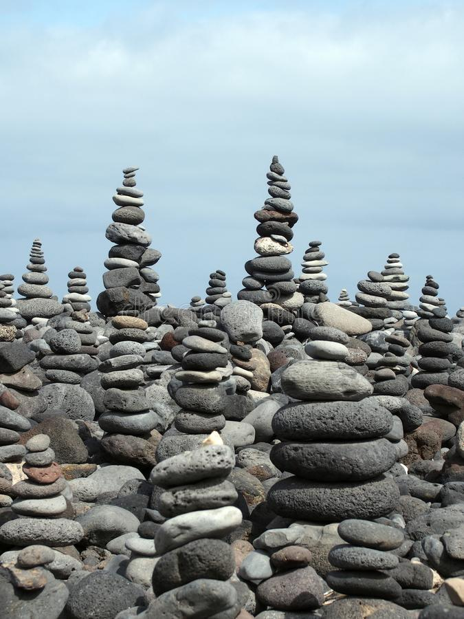 Rock art piles and towers of grey stones and pebbles on a beach stock photography