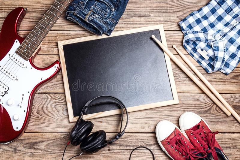Rock background with music equipment, clothes and footwear on wooden table with clean blackboard. royalty free stock photos