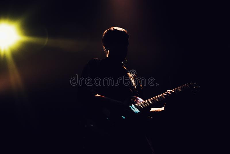 Rock band performs on stage. Guitarist plays solo. silhouette of guitar player in action on stage in front of concert crowd. Close-up. Dark background. Smoke royalty free stock image