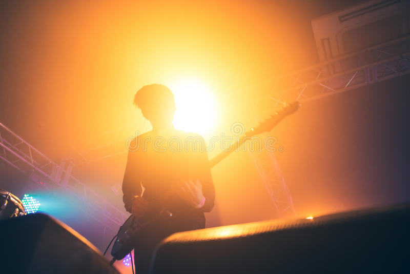 Rock band performs on stage. Guitarist plays solo. silhouette of guitar player in action on stage in front of concert crowd. Close-up. Dark background. Smoke