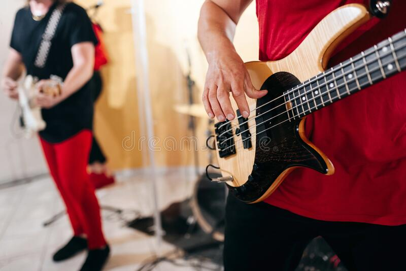 Rock band studio rehearsal. Male musician playing bass guitar before live concert. Rock band studio rehearsal. Male musician playing bass guitar before concert stock photos
