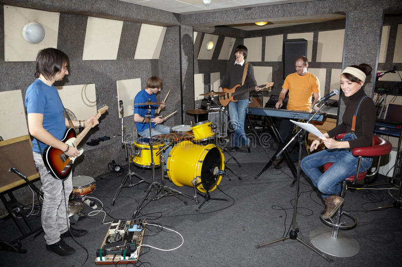 A rock band working in studio. A rock band. vocalist girl, two musicians with electro guitars, keyboarder and one drummer working in studio stock photo