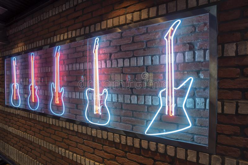 Rock Bar Neon decoration of Guitars on Brick Wall. Illuminated stock photos