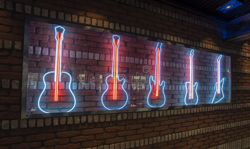 Rock Bar Neon decoration of Guitars on Brick Wall. Illuminated royalty free stock images