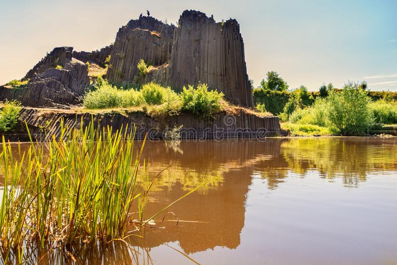 Rock of basalt with reflection on water lake. Famous landscape landmark called Panska skala at Kamenicky Senov at north of Czech Republic, 150 km north of stock image