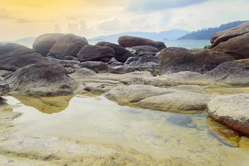 Rock beach. Flooding in the rocks niche at Koh Lipe beach, southern Thailand, shallow focused royalty free stock photo