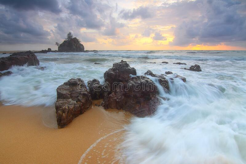 Rock on Beach Shore With Waves Crashing during Cloudy Daytime Sky royalty free stock photo