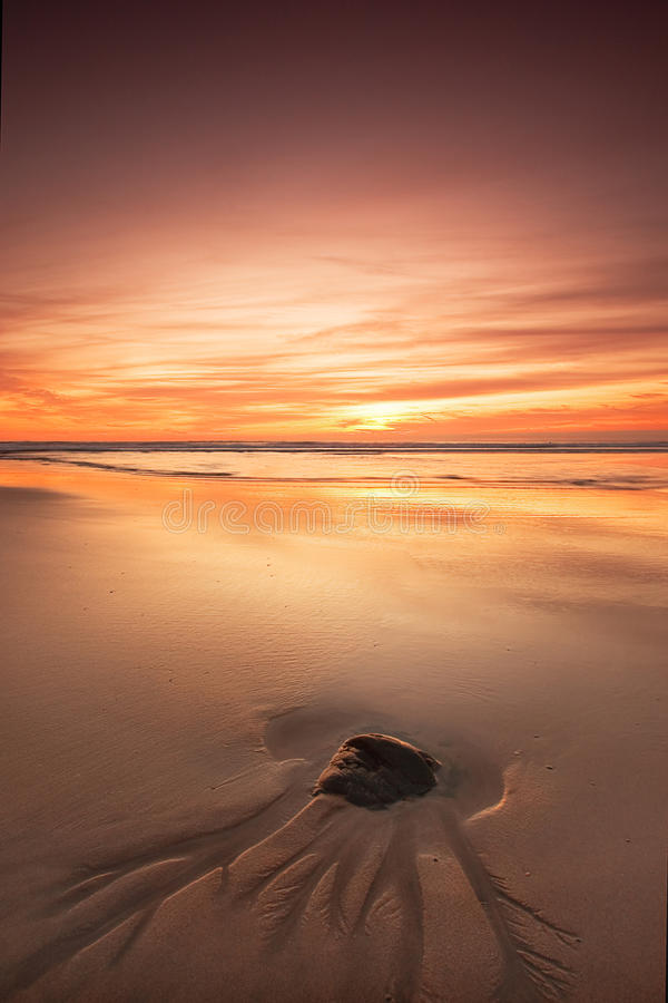 Rock on beach at sunset. Focus on a single rock on a long, sandy beach at sunset royalty free stock photos