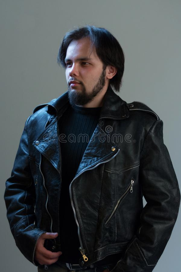 Rock or biker style. Portrait of a brutal guy with a beard in a black leather jacket. stock image