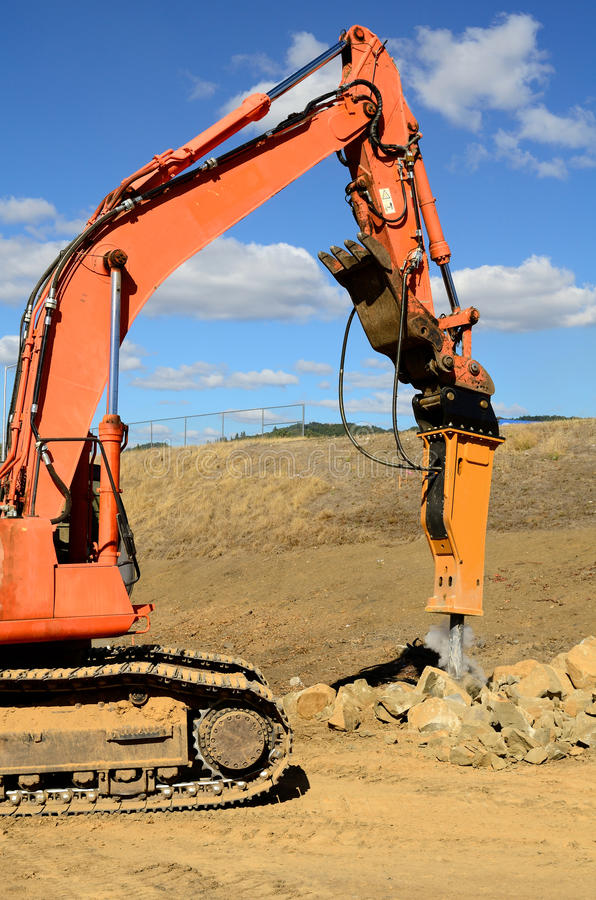 Rock Break. A large hydraulic rock breaker ram hammer installed on a track hoe excavator being used to break up stones at a new commercial construction stock photography