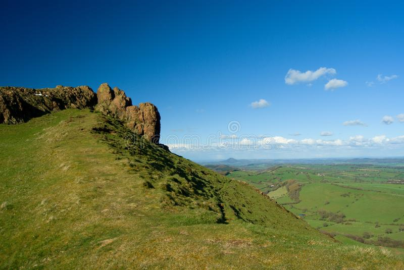 Rock of the Caer Caradoc, volcanic british and welsh hill. Rock of the Caer Caradoc, volcanic hill, english and welsh nature, blue polarised cloudy sky royalty free stock image