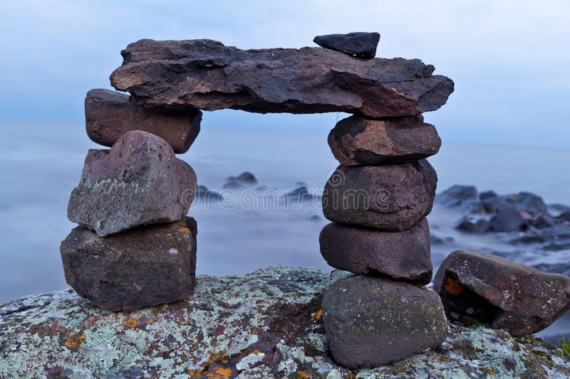 Rock cairn on the lakeshore. Warm summer evening at Lake Superior. Trail cairn on mossy stock photo
