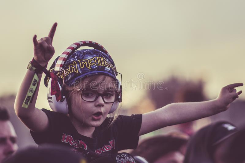 Rock child with horns up. In a heavy metal festival concert stock image