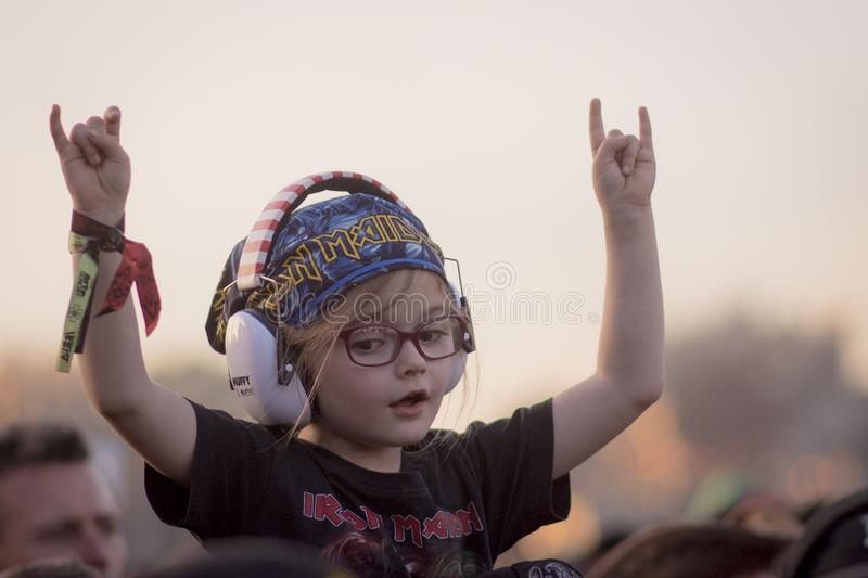 Rock child with horns up. In a heavy metal festival concert stock photos