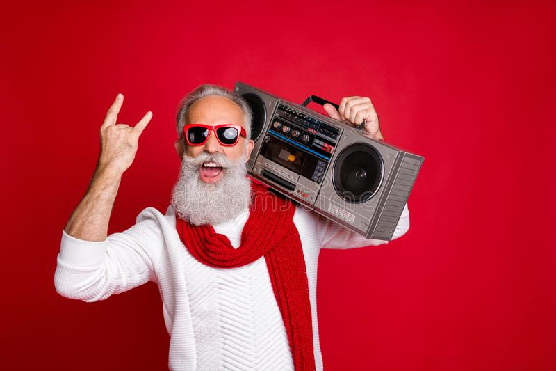 Rock chritmastime Portrait of crazy santa in eyeglasses eyewear screaming showing swag sign holding boom box wearing. Rock chritmastime Portrait of crazy santa royalty free stock photography