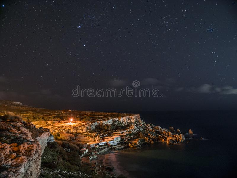 Rock Cliff Near Body of Water Under Clouds and Sky during Nighttime royalty free stock images