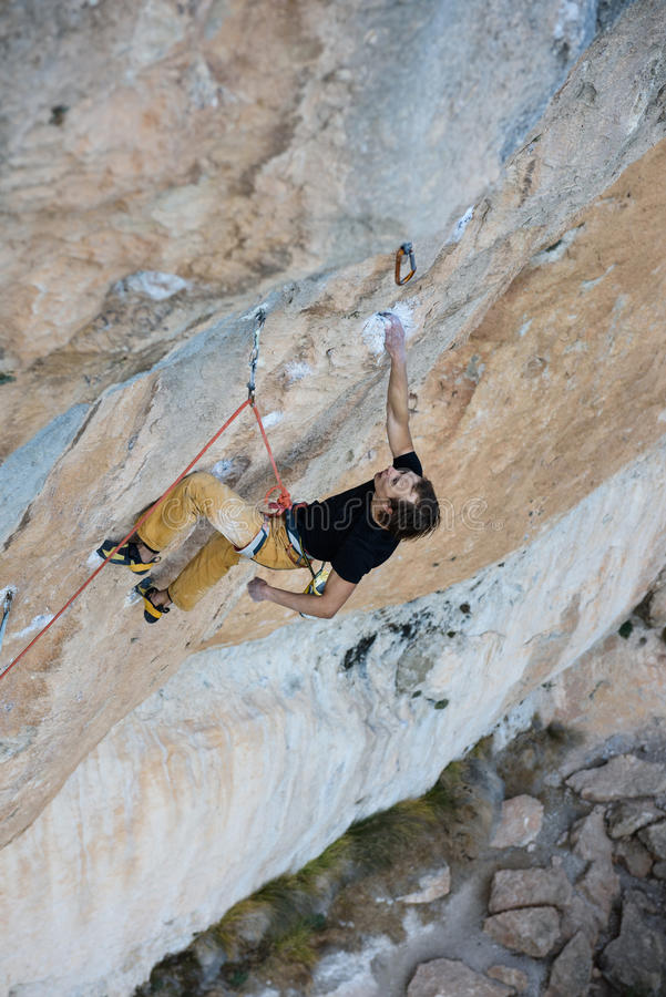 Rock climber ascending a challenging cliff. Extreme sport climbing. Freedom, risk, challenge, success. Sport and active stock image