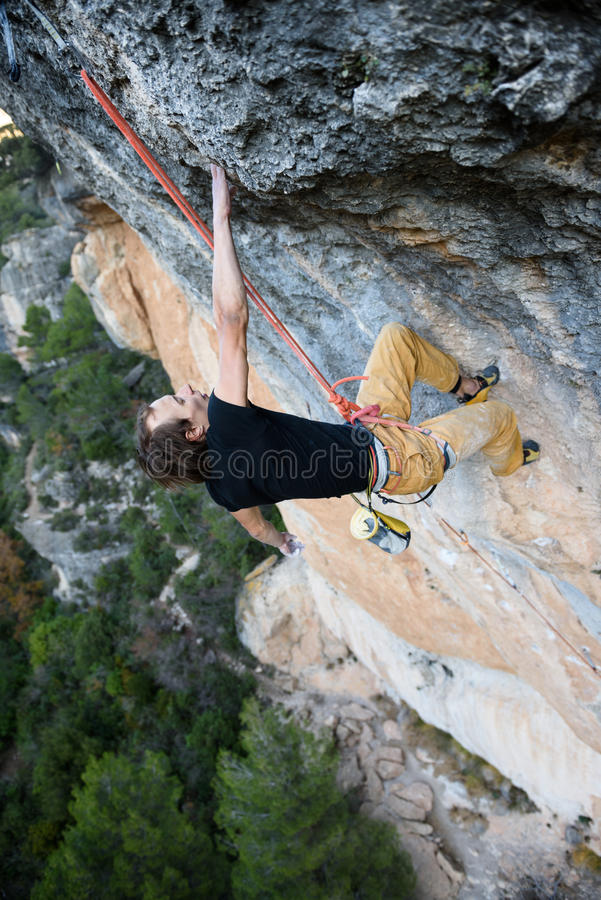 Rock climber ascending a challenging cliff. Extreme sport climbing. Freedom, risk, challenge, success. Sport and active royalty free stock images